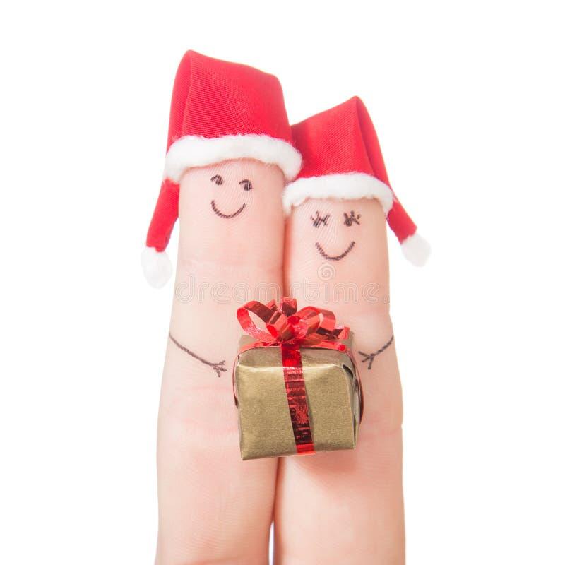 Caras de los fingeres en los sombreros de Papá Noel con la caja de regalo imagenes de archivo