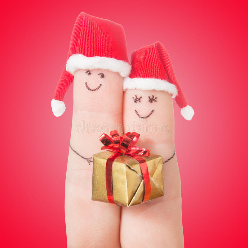 Caras de los fingeres en los sombreros de Papá Noel con la caja de regalo Pares felices foto de archivo libre de regalías
