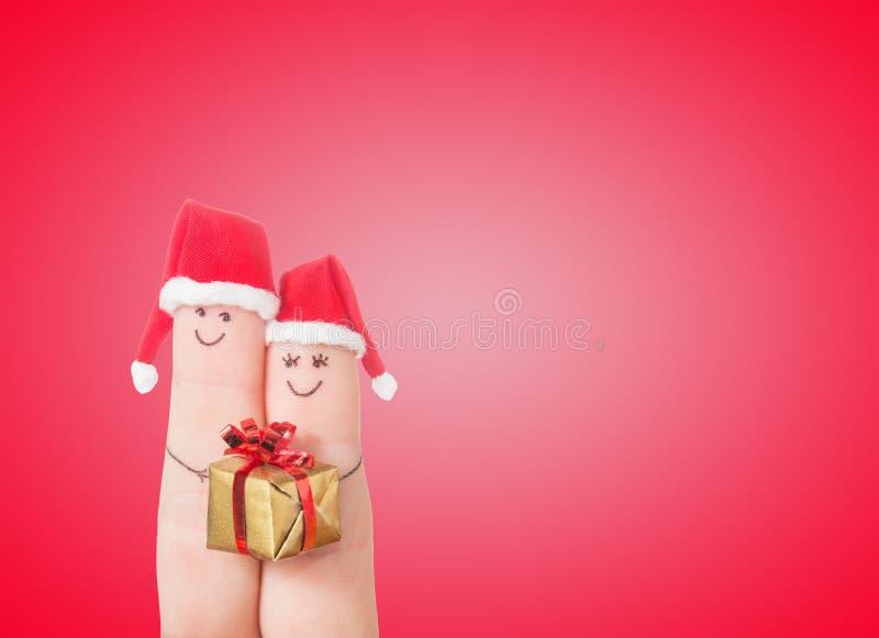 Caras de los fingeres en los sombreros de Papá Noel con la caja de regalo Pares felices fotos de archivo
