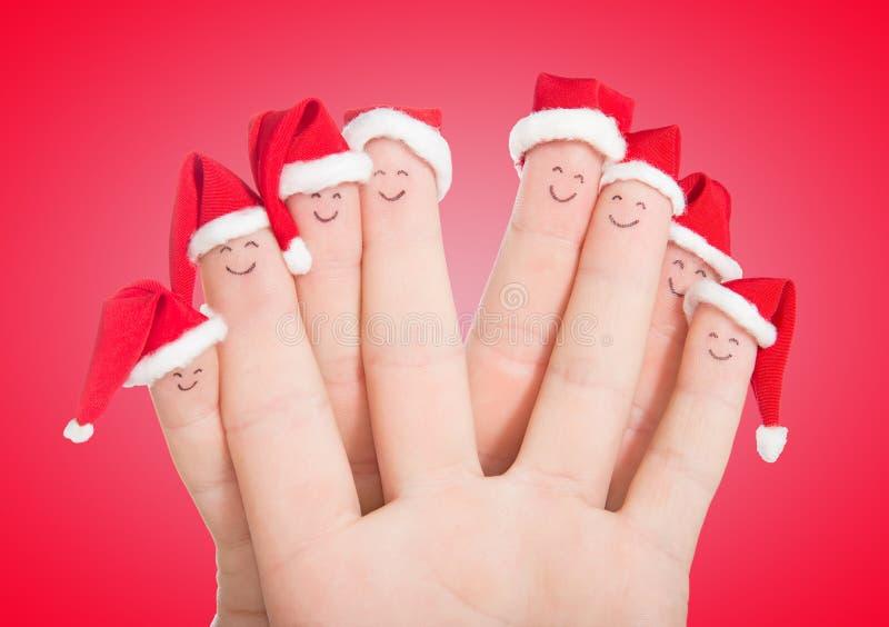 Caras de los fingeres en los sombreros de Papá Noel Familia feliz que celebra imagen de archivo