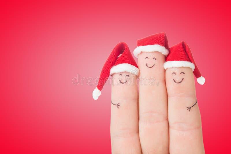Caras de los fingeres en los sombreros de Papá Noel Familia feliz que celebra fotografía de archivo libre de regalías