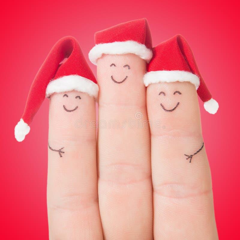Caras de los fingeres en los sombreros de Papá Noel Familia feliz que celebra fotos de archivo libres de regalías