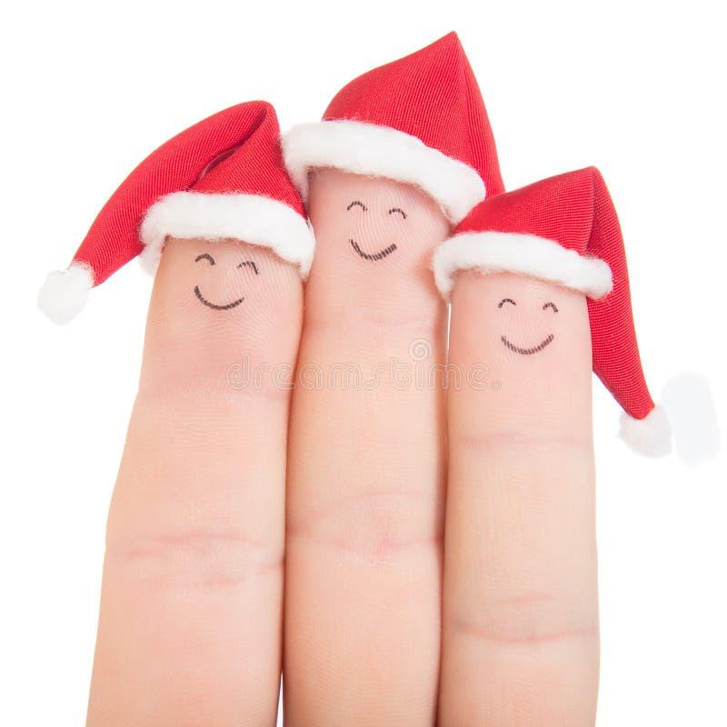 Caras de los fingeres en los sombreros de Papá Noel Familia feliz que celebra concepto fotografía de archivo