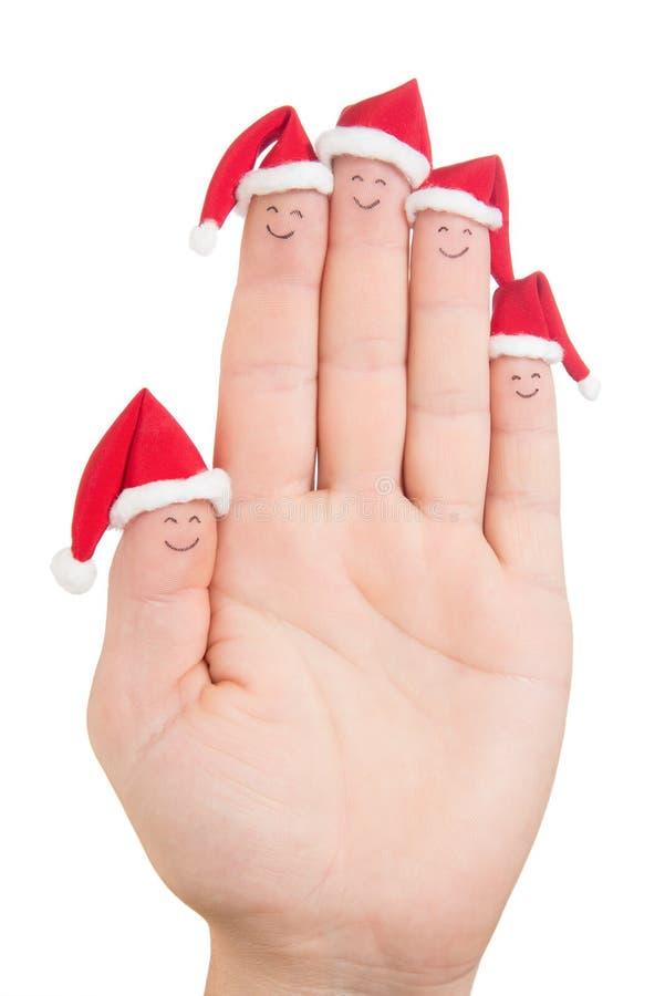 Caras de los fingeres en los sombreros de Papá Noel Familia feliz que celebra concepto foto de archivo libre de regalías