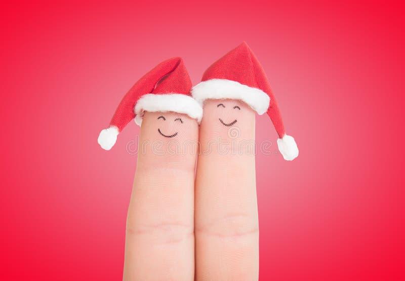 Caras de los fingeres en los sombreros de Papá Noel Pares felices que celebran fotografía de archivo libre de regalías