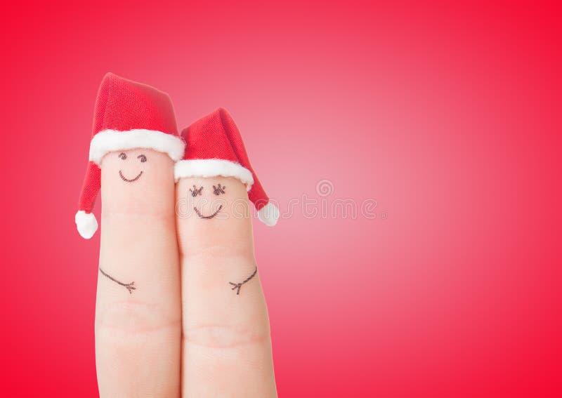 Caras de los fingeres en los sombreros de Papá Noel Pares felices que celebran imagenes de archivo