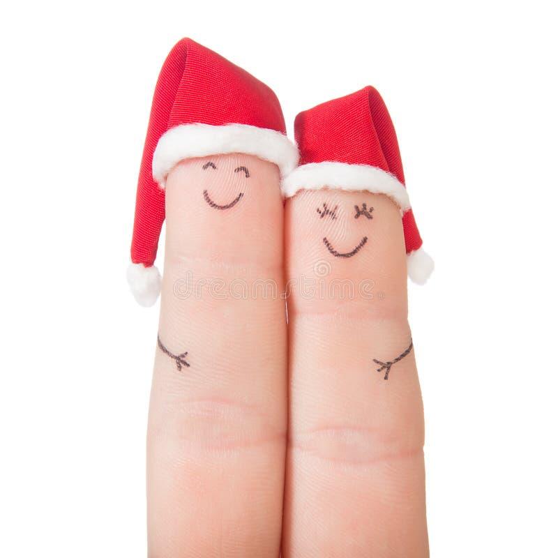 Caras de los fingeres en los sombreros de Papá Noel Pares felices que celebran concepto imagenes de archivo