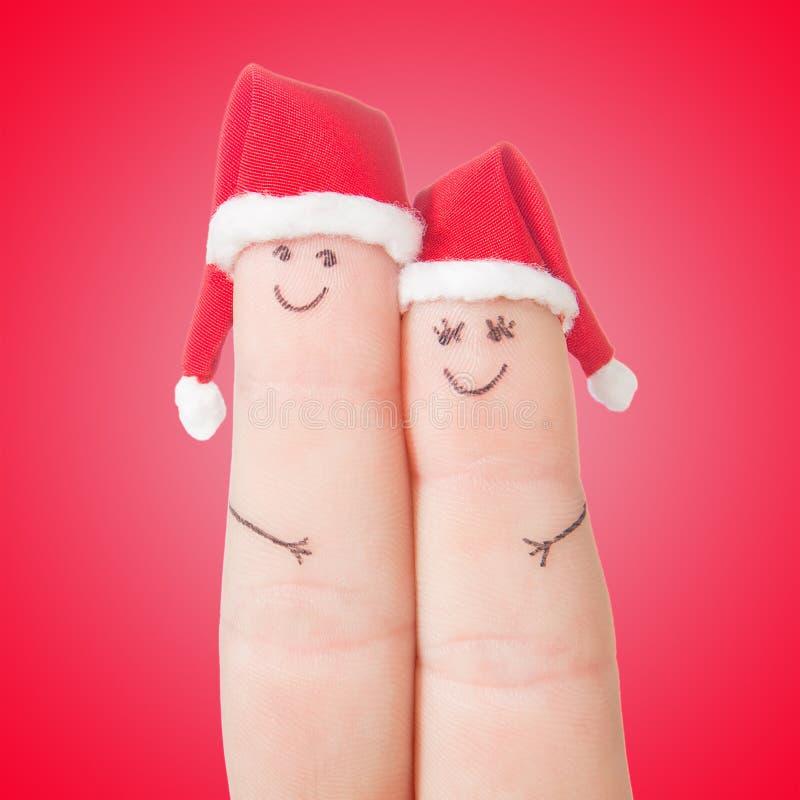 Caras de los fingeres en los sombreros de Papá Noel Pares felices que celebran concepto fotografía de archivo