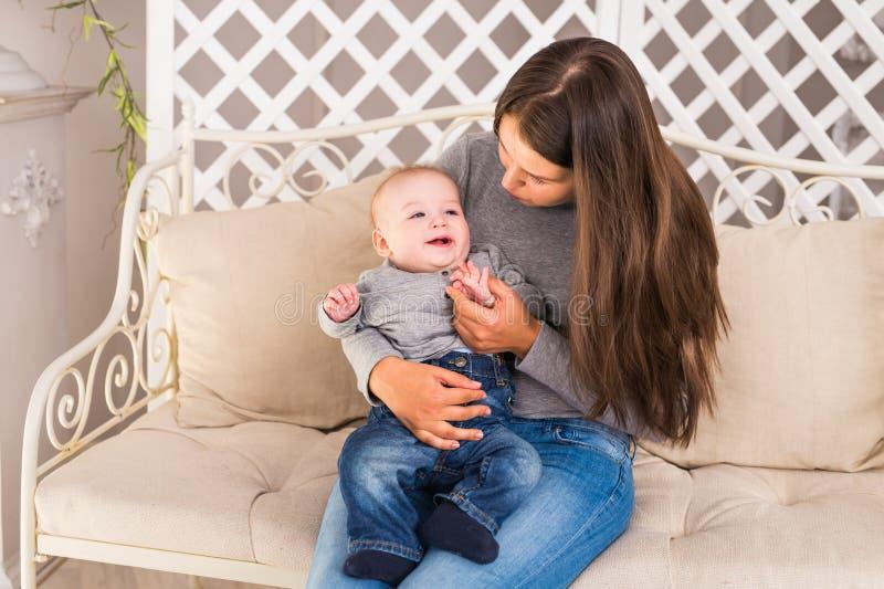 Caras de risa de la familia feliz, madre que celebra al bebé adorable del niño, sonriendo y abrazando, mamá alegre del niño sano imagenes de archivo