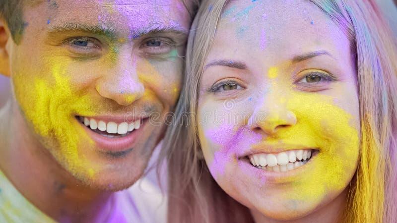 Caras de sorriso felizes, jovens alegres que olham o close up da câmera, festival da cor fotografia de stock