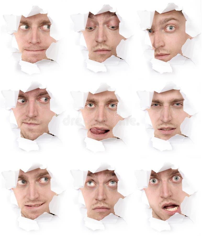 Caras del hombre en un agujero de papel imágenes de archivo libres de regalías