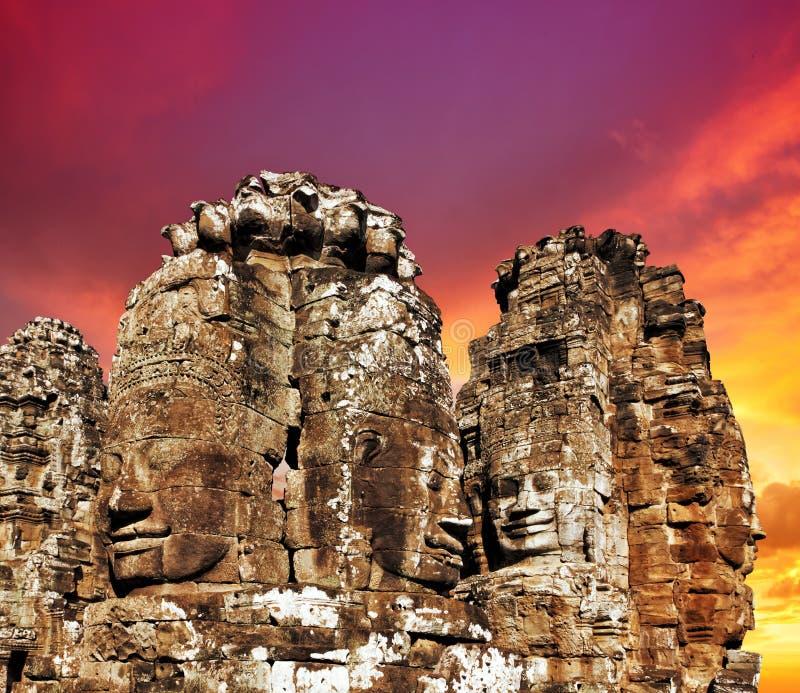 Caras del templo antiguo de Bayon en puesta del sol imagenes de archivo