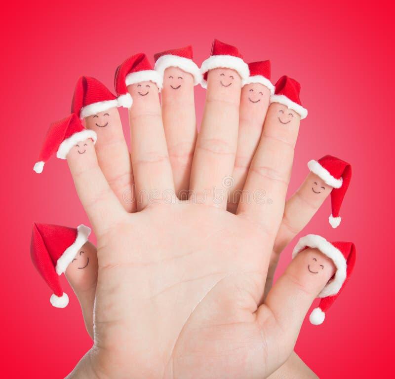 Caras dos dedos em chapéus de Santa Família feliz que comemora o conceito FO imagens de stock royalty free