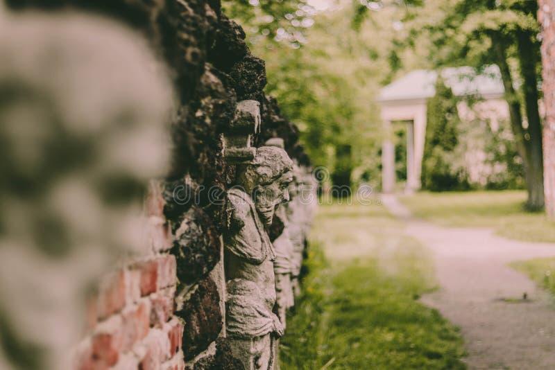 Caras en la pared en el parque, Arkadia Polonia imagenes de archivo
