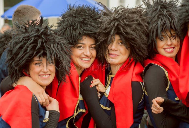 Caras felices de chicas jóvenes en trajes georgianos tradicionales en muchedumbre durante partido imagenes de archivo