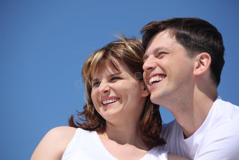 Caras felices de los pares en el cielo imagenes de archivo