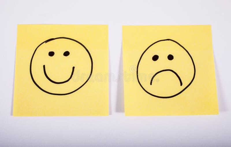 Caras felices y tristes en el papel de la nota imagen de archivo libre de regalías