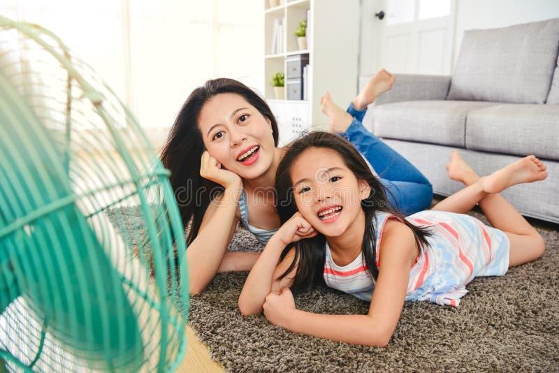 Caras refrigerando asiáticas felizes da mamã e da criança pelo fã fotografia de stock royalty free