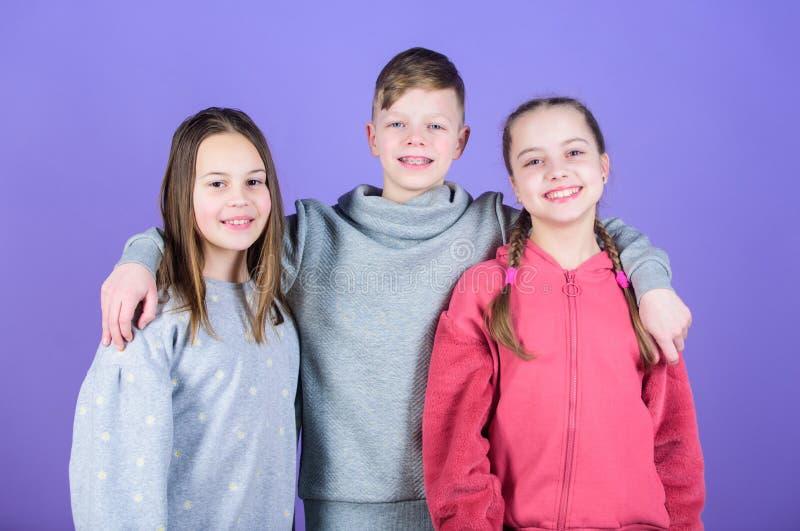 Caras sonrientes de los ni?os en el fondo violeta Los amigos abrazan El d?a de los ni?os Juventud alegre Relaciones y amistad Fel fotos de archivo libres de regalías