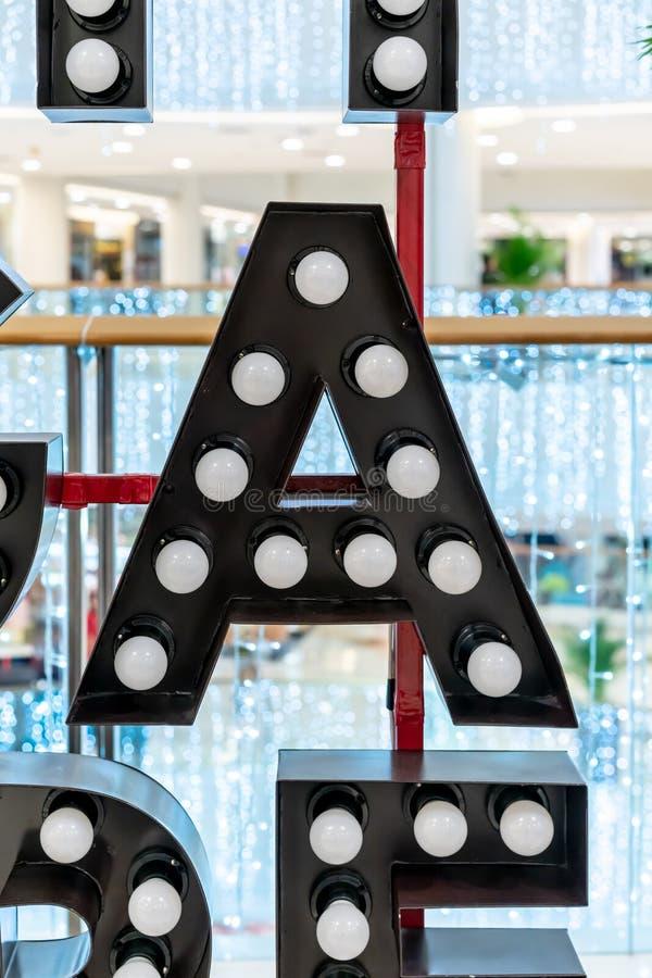 Carattere A di alfabeto della lettera nera della lampadina che appende sulla struttura rossa del metallo fotografia stock libera da diritti