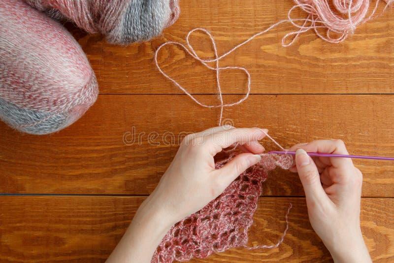 Carattere: donna che lavora a maglia una sciarpa con filetto rosa fotografia stock libera da diritti