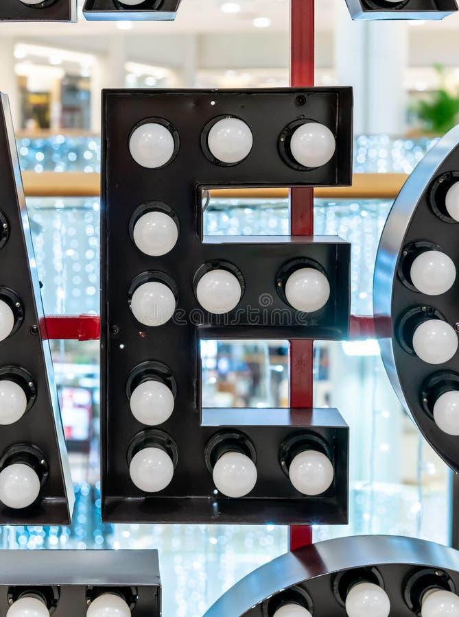 Carattere E di alfabeto della lettera nera della lampadina che appende sulla struttura rossa del metallo immagini stock