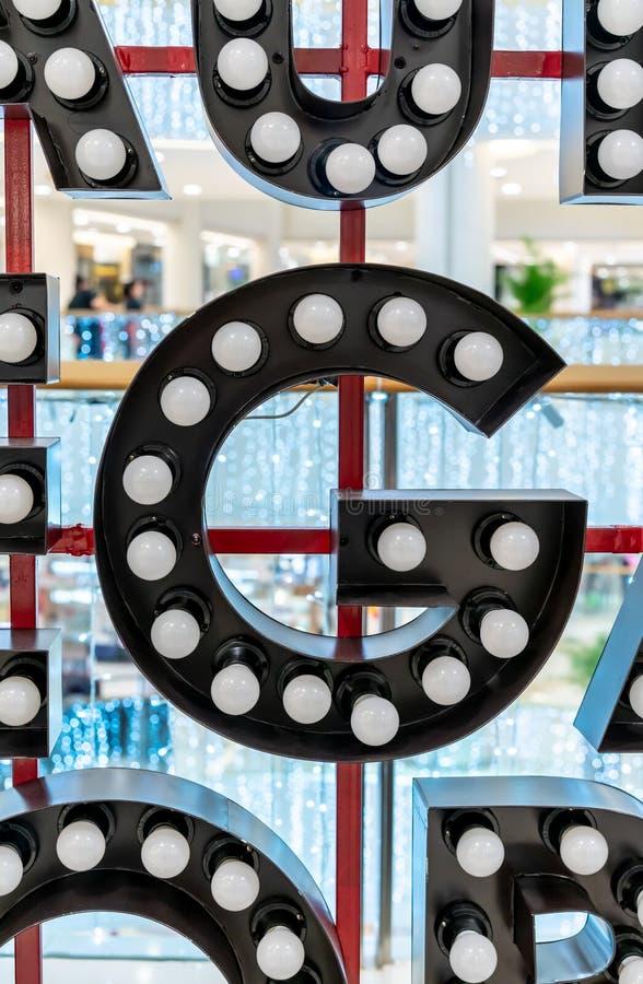 Carattere G di alfabeto della lettera nera della lampadina che appende sulla struttura rossa del metallo fotografie stock libere da diritti