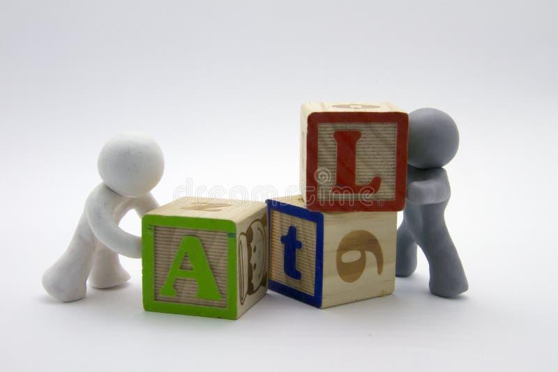 Caratteri della plastilina e cubi di legno immagine stock