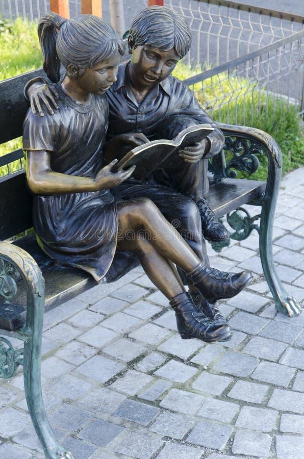 Caratteri di storia dei fratelli di Grimms su un banco di parco immagini stock libere da diritti