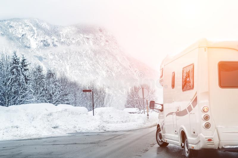 Caravan or campervan turning from road with beautiful mountain alpine landscape on background at cold winter season.Family royalty free stock images