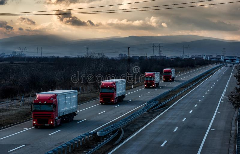 Caravan or convoy of lorry trucks on country highway royalty free stock photos