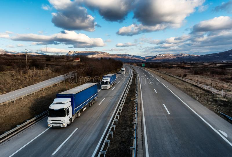 Caravan or convoy of lorry trucks on country highway stock image