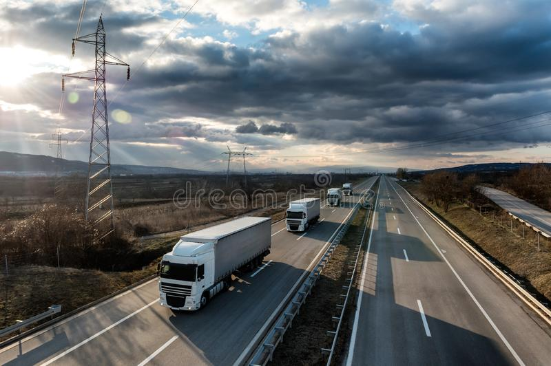 Caravan or convoy of lorry trucks on country highway royalty free stock photo