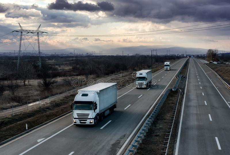 Caravan or convoy white lorry trucks on country highway royalty free stock images