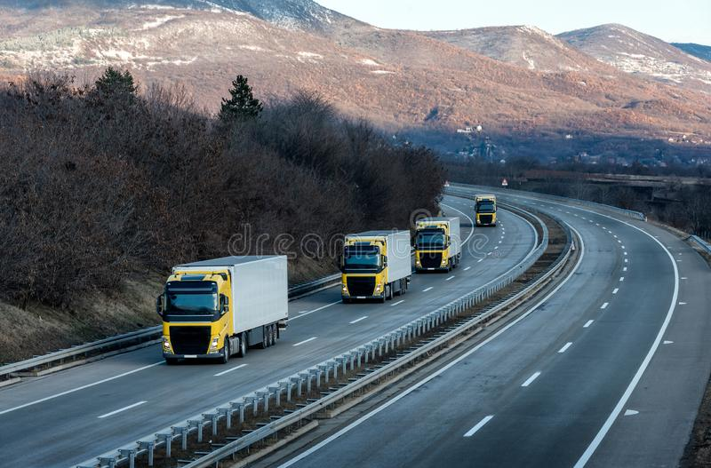 Caravan or convoy of Yellow lorry trucks on country highway royalty free stock photos