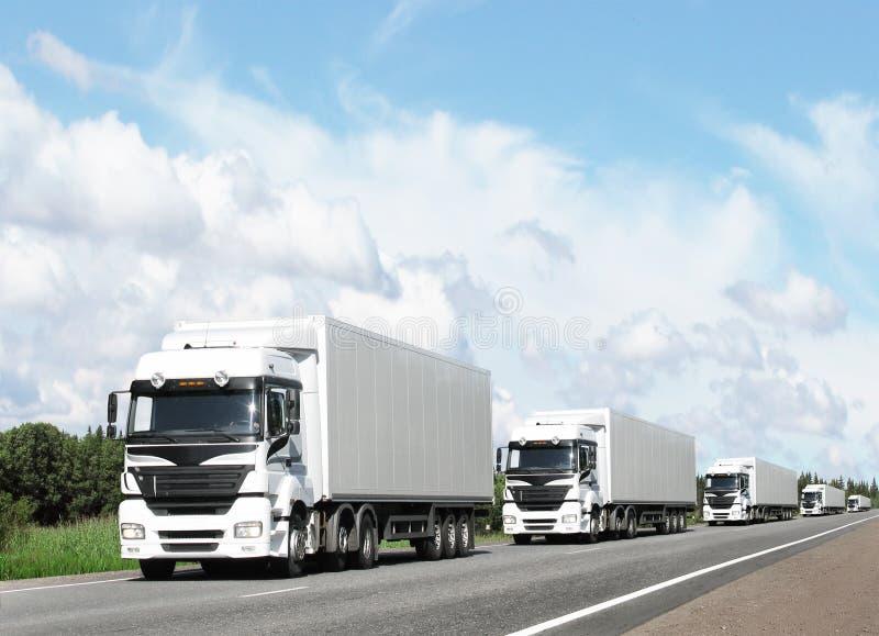 Caravan dei camion bianchi sulla strada principale immagini stock libere da diritti