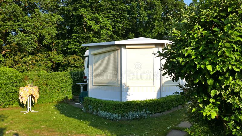 Caravan with a fixed veranda made of awning fabric, glass sliding windows and blinds on a German campsite. stock photography