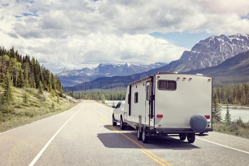Caravan or motor home trailer on a mountain road royalty free stock photography