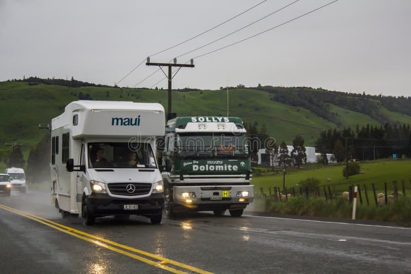 Caravan overtaking truck on wet road stock images