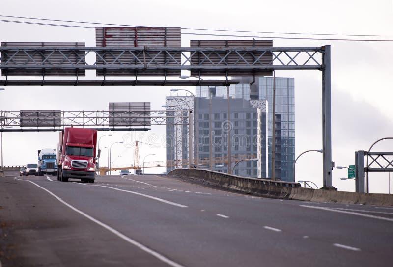 Caravan van semi vrachtwagens die door brede weg gaan tusen staten royalty-vrije stock fotografie