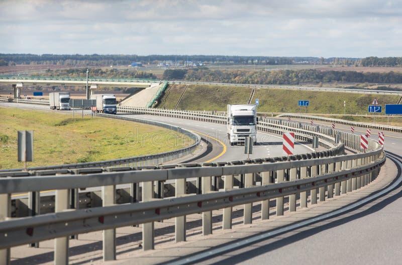 Caravan van witte vrachtwagensbeweging op de weg van het land stock fotografie