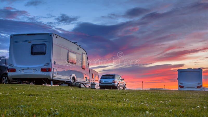 Caravana e por do sol dos carros fotografia de stock royalty free