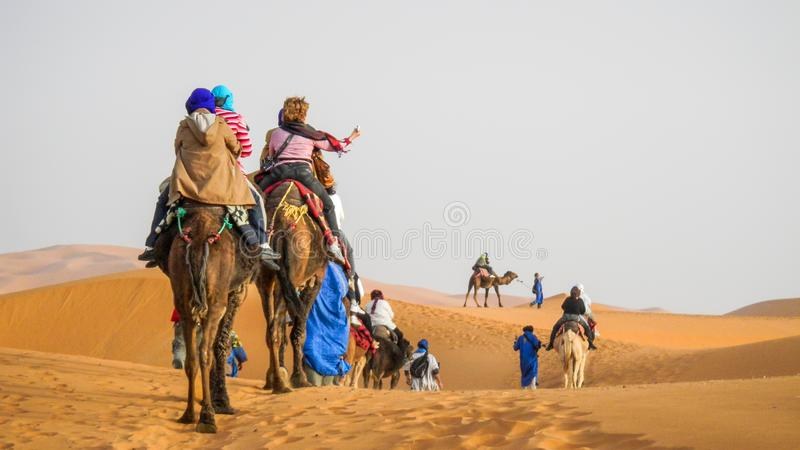 Caravana que pasa a través de las dunas de arena en Sahara Desert, Marruecos del camello fotografía de archivo