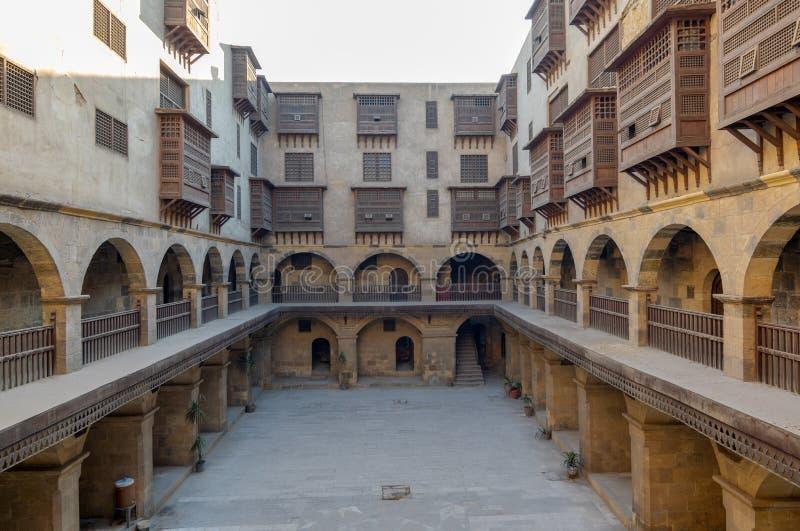 Caravansary Wikala di Bazaraa, con le gallerie arcate e le finestre coperte dal mashrabiyya di legno interfogliato di griglie, Il immagine stock