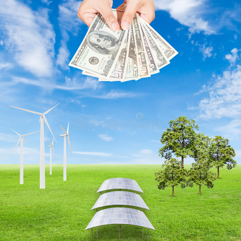 Carbon credits concept. Hand holding wind turbine, solar panels, tree and US Dollars banknote against green field and blue sky background royalty free stock image