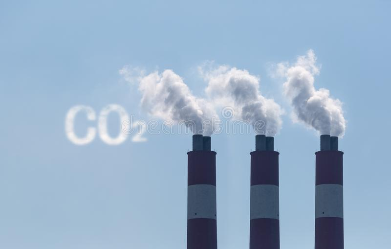 Carbon dioxide emission. Factory chimneys with symbolic emission of a CO2 cloud royalty free stock image