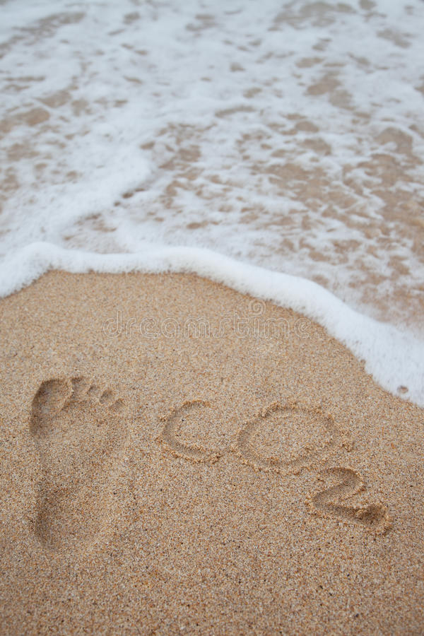 Carbon footprint concept. Footprint and carbon dioxide imprints on the beach stock photos