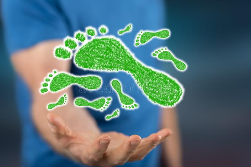 Concept of carbon footprint. Carbon footprint concept above the hand of a man in background royalty free stock photo