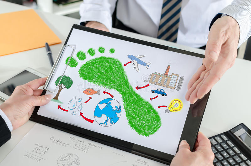 Carbon footprint concept on a clipboard. Carbon footprint concept shown by a businessman royalty free stock photos