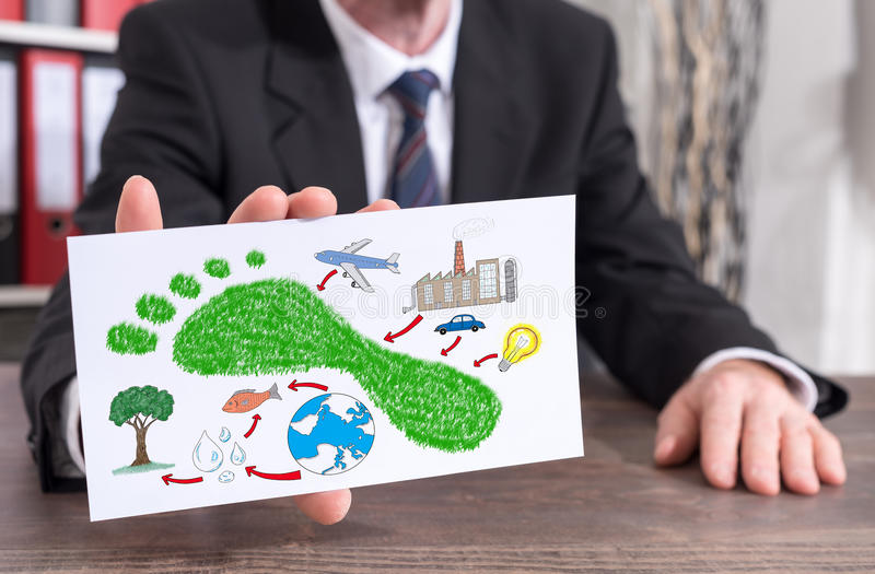Carbon footprint concept on an index card. Businessman showing an index card with carbon footprint concept stock image